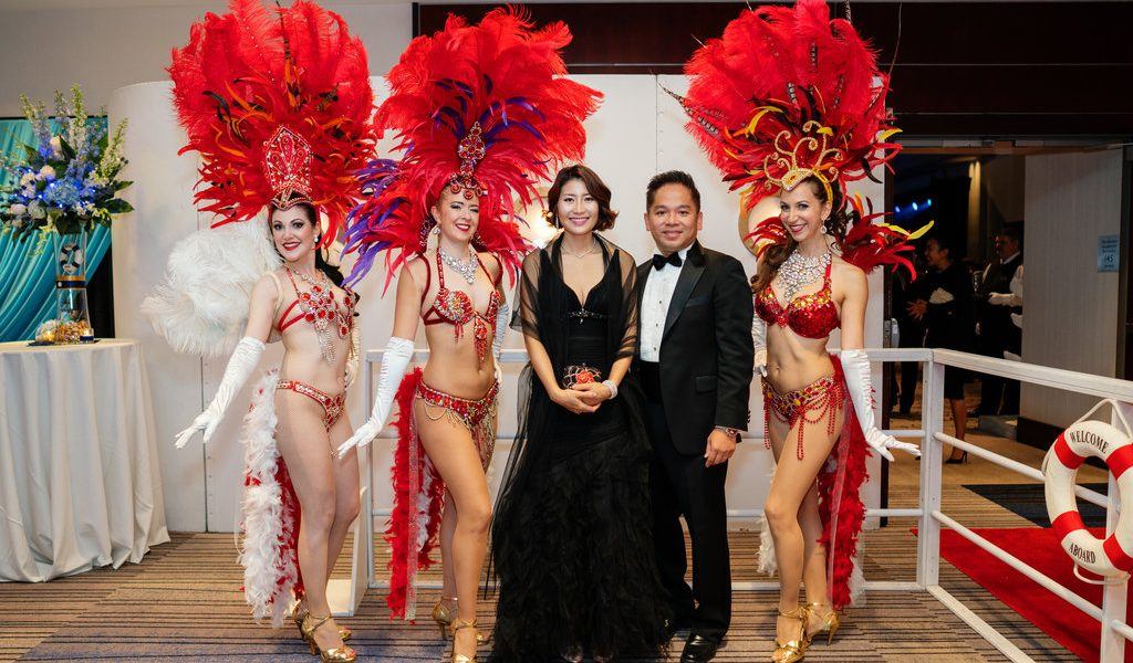 Our showgirls in red costume posing with guests at a gala event in Vancouver, B.C.